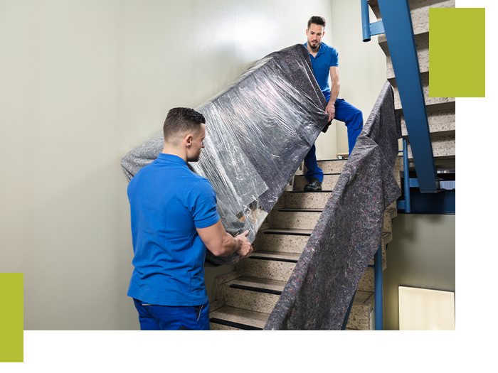 Two movers carrying a plastic-wrapped piece of furniture up the stairs.